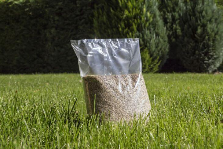 Plastic bag with grass seed that is going to be used for reseeding the lawn.