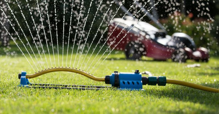 Grass mower and a sprinkler watering grass.