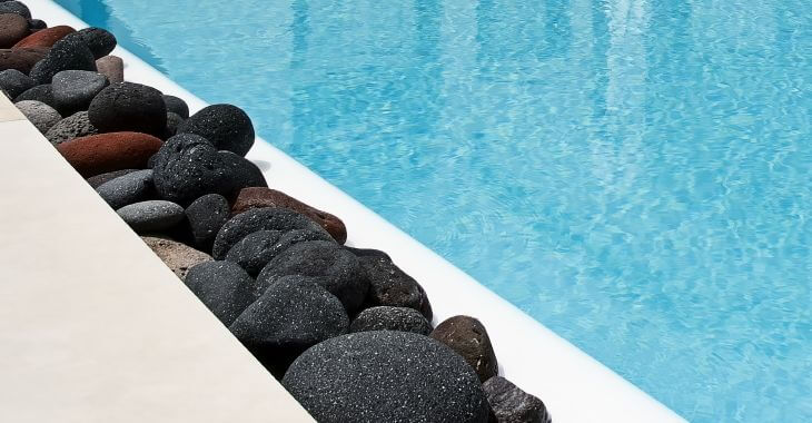 Color lava rocks on the side of the backyard swimming pool.