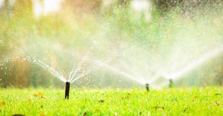 Working sprinkler system watering autumn lawn.