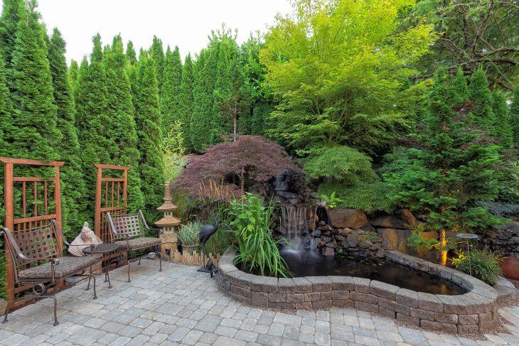 Backyard flagstone patio with hardscapes made od different types of landscaping stones.